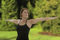 Kvinnan som gör den yogaAsana krigaren, poserar Royaltyfria Foton