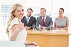 Kvinnan som gör en gest tummar, up framme av företags personaltjänstemän Arkivfoton
