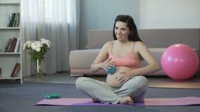 Kvinnan som gör massage till hennes mage med, behandla som ett barn inom med små konditionbollar lager videofilmer