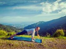 Kvinnan som gör plankan för den Hatha yogaasanaen, poserar utomhus Fotografering för Bildbyråer