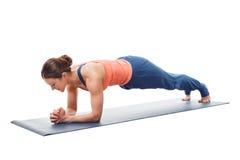 Kvinnan som gör plankan för den yogaasanaChaturanga dandasanaen, poserar Arkivfoto