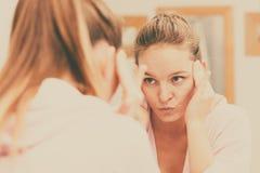 Kvinnan som gör ren hennes framsida med, skurar i badrum arkivfoto