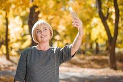 Kvinnan som gör selfie på en bakgrund av hösten, parkerar Royaltyfri Foto