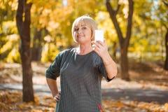 Kvinnan som gör selfie på en bakgrund av hösten, parkerar Bekläda beskådar Royaltyfri Bild