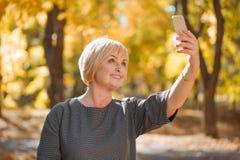 Kvinnan som gör selfienärbild på en bakgrund av hösten, parkerar Arkivbild