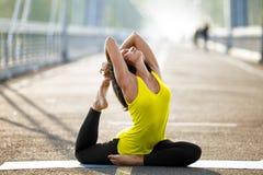Kvinnan som gör sträcka yoga, övar utomhus Royaltyfri Bild
