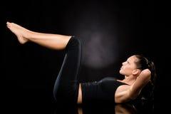 Kvinnan som gör sträckning, övar med lyftt lägger benen på ryggen Royaltyfria Bilder