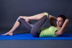 Kvinnan som gör styrka, övar för buk- muskler över grå färger Fotografering för Bildbyråer
