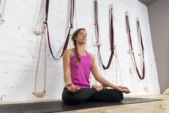Kvinnan som gör yoga, övar i idrottshallen, sportkonditionflickan som sitter Lotus Pose Royaltyfri Fotografi