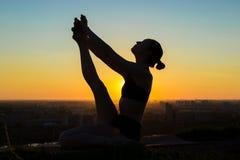 Kvinnan som gör yoga, i att sväva fartyget, poserar i parkera på solnedgången Arkivfoton