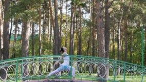 Kvinnan som gör yoga i, parkerar på bron Sund livsstil stock video