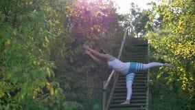 Kvinnan som gör yoga i, parkerar på trappan Solstrålar arkivfilmer