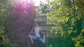 Kvinnan som gör yoga i, parkerar på trappan Solstrålar stock video