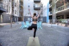 Kvinnan som gör yoga, poserar utanför Fotografering för Bildbyråer