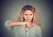 Kvinnan som ger tummen gör en gest ner, att se med negativt uttryck Royaltyfri Foto
