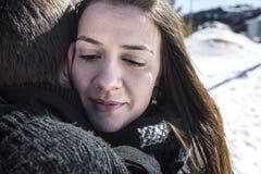 Kvinnan som gråter nära man i vinter och torkar, river av hennes framsida Arkivbild