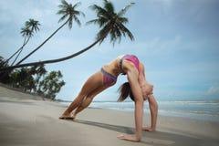 Kvinnan som gör yogabron, poserar på stranden Arkivfoto