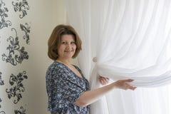 Kvinnan som hänger upp hans vit, hänger upp gardiner på fönstret Royaltyfri Bild