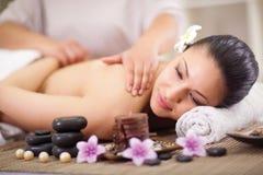 Kvinnan som har en wellness tillbaka, masserar Arkivfoton