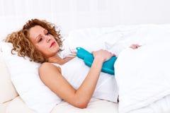 Kvinnan som har magen, smärtar royaltyfria foton