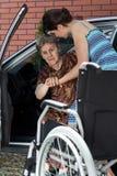 Kvinnan som hjälper hennes farmor, får in i bilen Arkivfoto