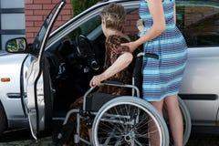 Kvinnan som hjälper en handikappade personerdam, får i bilen Arkivbilder