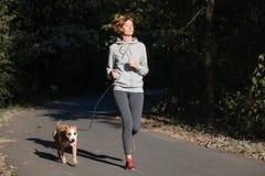 Kvinnan som joggar med hunden i, parkerar Ung kvinnlig person med husdjur D arkivbild