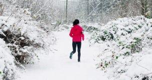 Kvinnan som joggar på snö, täckte banan under snöfall lager videofilmer