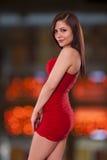 Kvinnan som kläs för en natt på staden, poserar framme av stadslig Royaltyfria Bilder