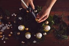 Kvinnan som klibbar jul, klumpa ihop sig med det varma vapnet på kransen Arkivfoton