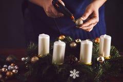 Kvinnan som klibbar jul, klumpa ihop sig med det varma vapnet på kransen Fotografering för Bildbyråer