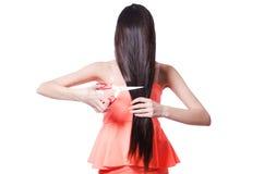 Kvinnan som klipper hennes hår som isoleras på vit Arkivbild