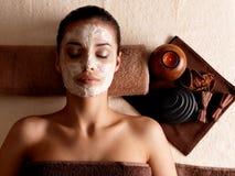 Kvinnan som kopplar av med ansiktsbehandling, maskerar vänder mot på på skönhetsalongen Royaltyfri Fotografi