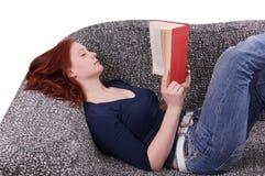 Kvinnan som kopplar av med, bokar på soffan arkivfoton