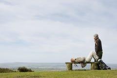 Kvinnan som kopplar av på, parkerar bänken med mannen som ser havet Arkivbild