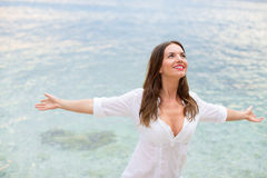 Kvinnan som kopplar av på stranden med armar, öppnar att tycka om hennes frihet Fotografering för Bildbyråer