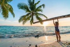 Kvinnan som kopplar av under kokosn?ten, g?mma i handflatan ormbunksbladet p? den sceniska vita sandstranden, den soliga dagen, g arkivbilder