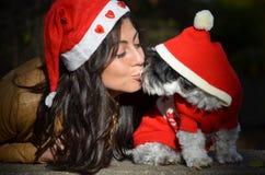 Kvinnan som kysser hennes hund, klädde med röda julhattar Arkivbilder