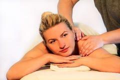 Kvinnan som lägger på massagetabellen och har en massage, knuffar fotografering för bildbyråer