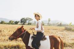 Kvinnan som ler med, kopplar av tid på liten häst Arkivbild