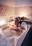 Kvinnan som in ligger, badar göra hydroterapibehandling Fotografering för Bildbyråer