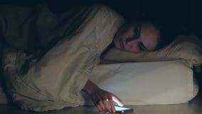 Kvinnan som ligger i säng, faller sätta sovande och vänder av smartphonen