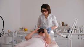 Kvinnan som ligger på en tabell med, skyddar exponeringsglas på ögon som får en laser-hudbehandling i sund skönhetbrunnsortsalong stock video