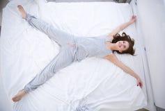 Kvinnan som ligger på sängen i stjärna, poserar Royaltyfri Fotografi