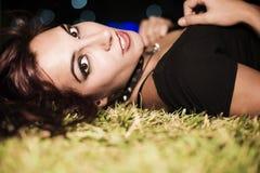 Kvinnan som in ligger, parkerar gräs med stadsnattljus Arkivfoto