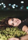 Kvinnan som in ligger, parkerar gräs med stadsnattljus Arkivfoton