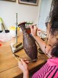 Kvinnan som limmar den mycket lilla formade cloisonnen, binder till en kopparvas arkivfoton