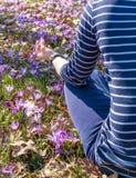 Kvinnan som mediterar i en yoga, poserar på gräsmattan med krokusar Royaltyfria Bilder