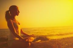Kvinnan som mediterar i lotusblomma, poserar på stranden på solnedgången Royaltyfria Foton