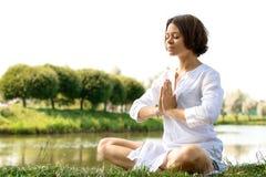 Kvinnan som mediterar i sukhasana, poserar på flod-banken Arkivfoton
